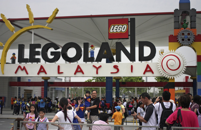 Visitors take photographs at the entrance to Legoland Malaysia, operated by Themed Attractions and Resorts Sdn., in Kota Iskandar, Johor, Malaysia, in 2012. (Bloomberg)