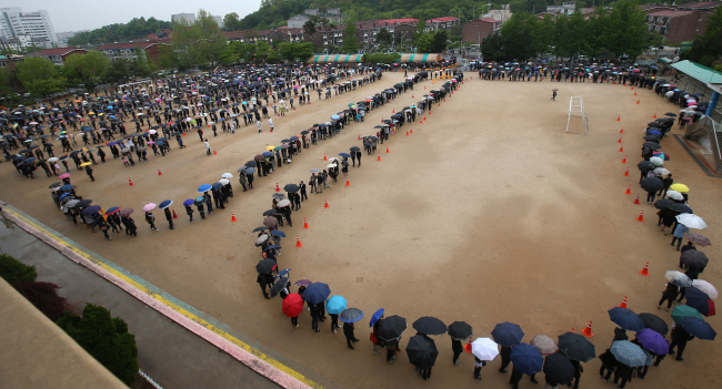 Mourners line up to visit the memorial altar in Ansan, Gyeonggi Province, Sunday. The playing field of a neighboring public school was used to accommodate the large number of visitors. (Yonhap)