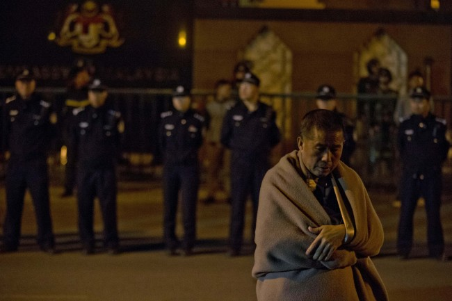 A relative of Chinese passengers onboard the Malaysia Airlines MH370 wrapped in a blanket against the cold, waits for embassy staff to meet their demands outside the Malaysian Embassy in Beijing. (AP-Yonhap)