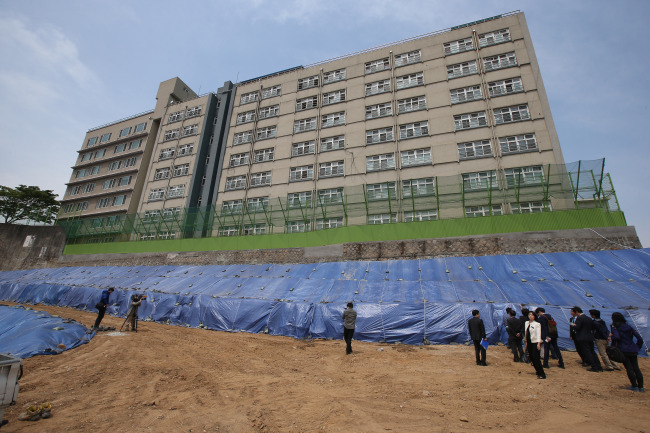 Officials examine a retaining wall at Hwanil Middle and High School in Seoul on May 7. (Yonhap)