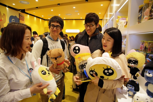 Customers hold KakaoTalk character dolls at the messenger service's pop-up store in Sincheondong,Seoul. (Kakao Corp.)