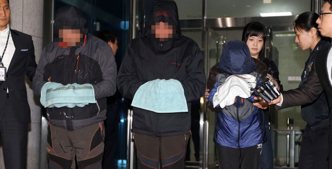 The captain (left) of the Sewol and other crew members walk out of a court room after attending a deliberation session on the issuance of arrest warrants against them last month. (Yonhap)