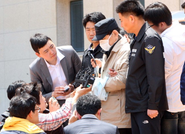 Reporters ask questions to Kim Han-shik, CEO of the sunken ferry Sewol's operator Chonghaejin Marine Co., as he leaves the Mokpo Branch of Gwangju District Court last Friday. (Yonhap)