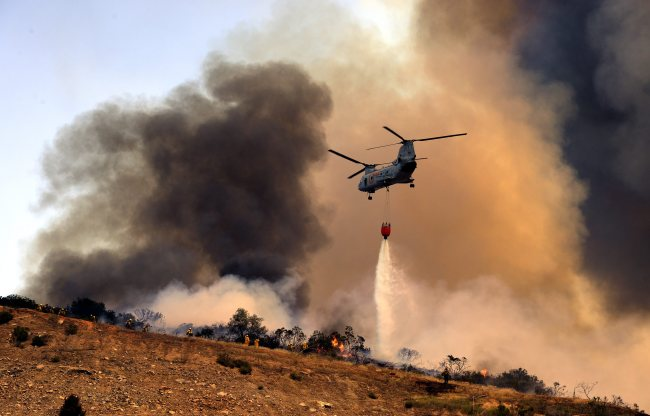 A U.S. military helicopter dumps water on a wildfire in San Marcos, California. (EPA-Yonhap)