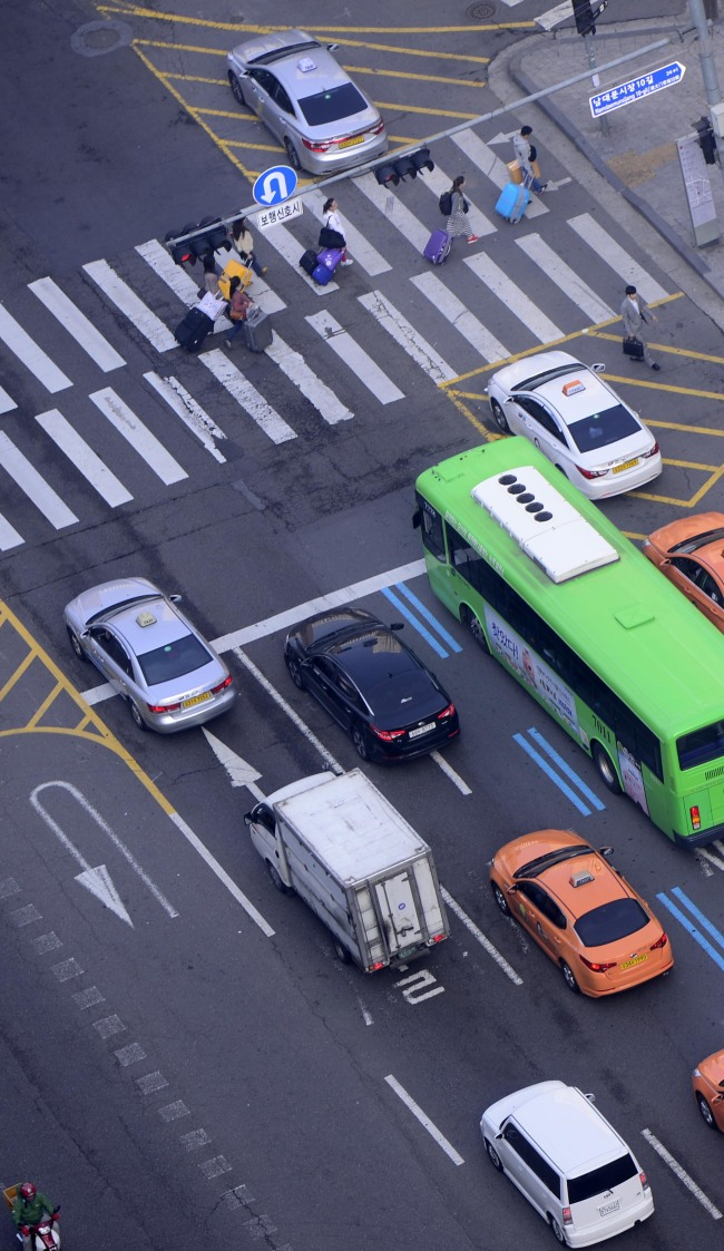 Pedestrians cross at a crosswalk where three vehicles went past the stop line.(Park Hae-mook/ The Korea Herald)
