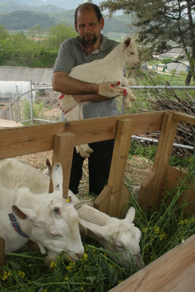 Doug Huffer poses with a kid on his goat farm near Gyeongju, North Gyeongsang Province. (Paul Kerry/The Korea Herald)