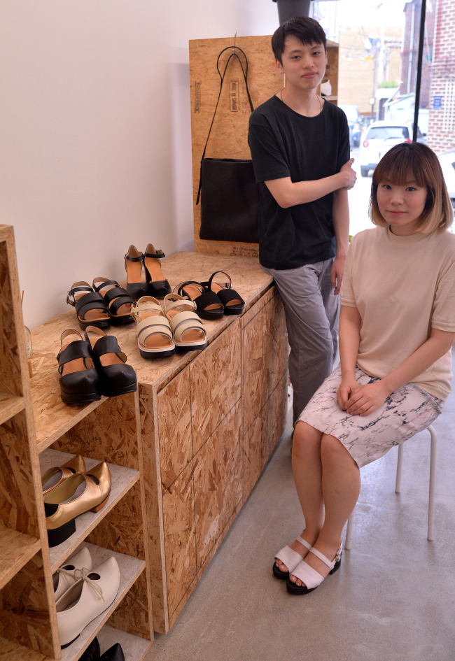 Flat Apartment cofounders Seo Kyung-hee (right) and Yie Kwang-sub pose with their shoes at their store in Sinsa-dong, Seoul. (Lee Sang-sub/The Korea Herald)