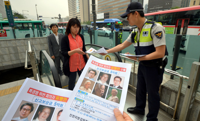 A policeman hands out posters of the wanted Yoo Byung-eon and his eldest son Dae-gyun to passersby in downtown Seoul on Monday. (Kim Myung-sub/The Korea Herald)