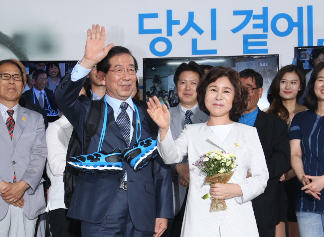 Seoul Mayor Park Won-soon and his wife Kang Nan-hee wave hands to his supporters after winning reelection on Thursday morning. (Yonhap)