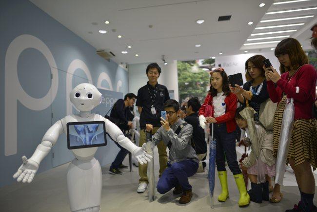 "Visitors look at humanoid robot ""Pepper"" in Tokyo on Saturday. (EPA-Yonhap)"