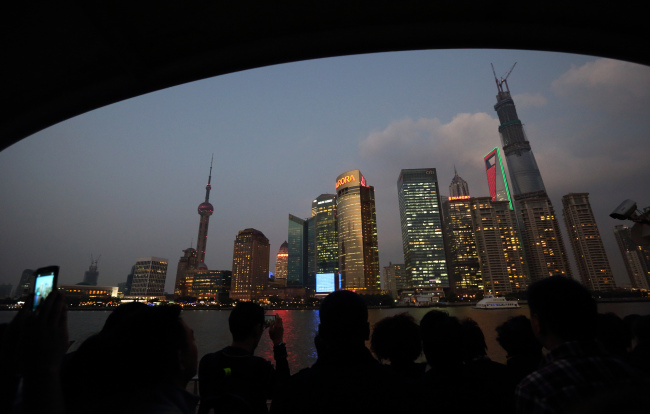 Passengers on a ferry look at buildings in Lujiazui district at dusk in Shanghai. (Bloomberg)