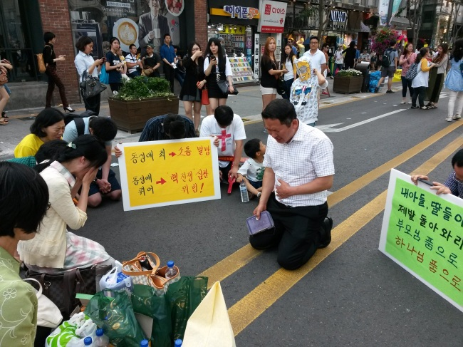 """Members of an antigay Christian group kneel in the street, crying and praying as they hold up signs declaring, """"Thesin of homosexuality will cause the end of the world,"""" during the 15th Korea Queer Cultural Festival in the Sinchon district of Seoul on June 7. (Philip Iglauer/The Korea Herald)"""