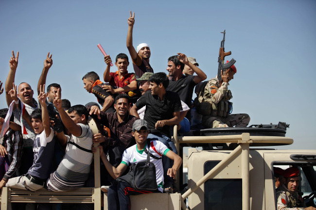 Iraqi men, who volunteered to fight against the Jihadist militants, gather around buses in Baghdad on Monday. (AFP-Yonhap)
