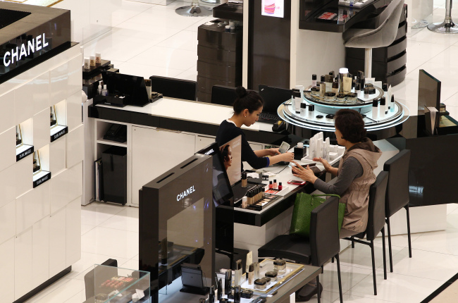 An employee serves a customer at the Chanel SA cosmetic booth in Shinsegae Centum City department store in Busan. (Bloomberg)