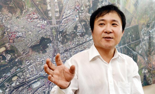 Writer Jang Jin-sung speaks at the New Focus International office in northeastern Seoul. Behind him is a satellite image of Pyongyang. (Park Hyun-koo/ The Korea Herald)