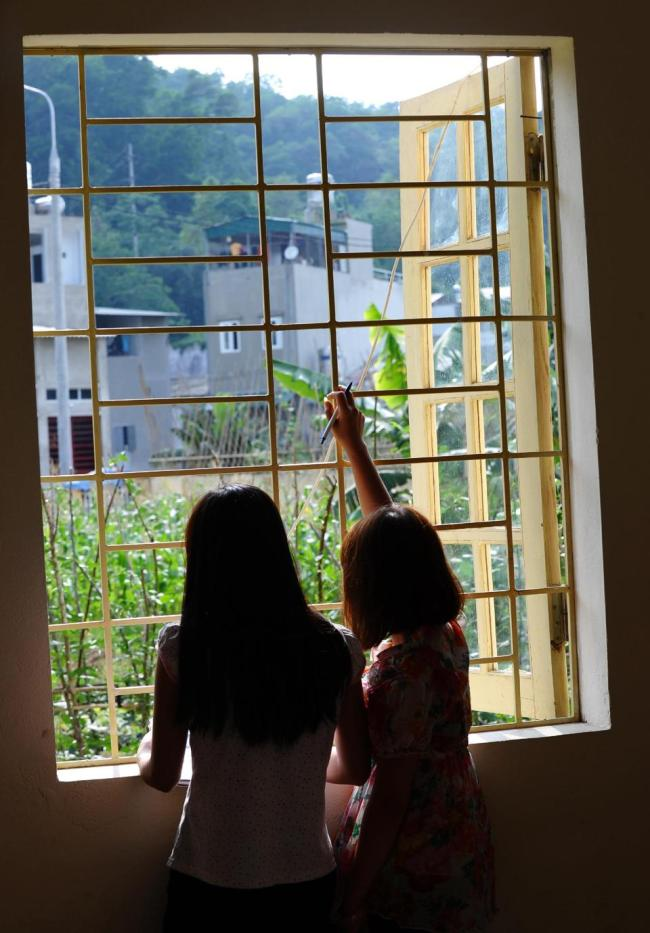 Teenager May Na (left) and a roommate look out from a window at a government-run center for trafficked women in the northern city of Lao Cai. (AFP)