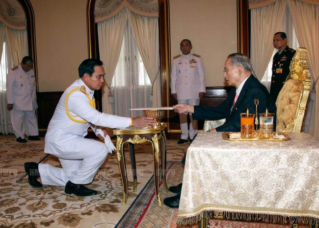 Army chief Gen. Prayut Chan-O-Cha (left) receives the interim constitution from King Bhumibol Adulyadej at the royal palace in Hua Hin, Thailand, Tuesday. (AFP-Yonhap)