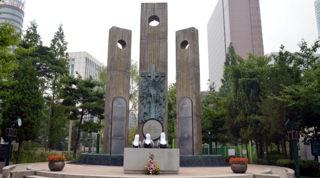 Nuns pray before a memorial tower dedicated to martyrs at Seosomun Martyrs' Shrine on Thursday. (Kim Myung-sub/The Korea Herald)