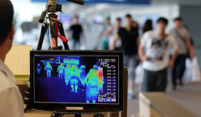 A quarantine officer monitors travelers' body temperatures at Incheon International Airport over the weekend. (Yonhap)