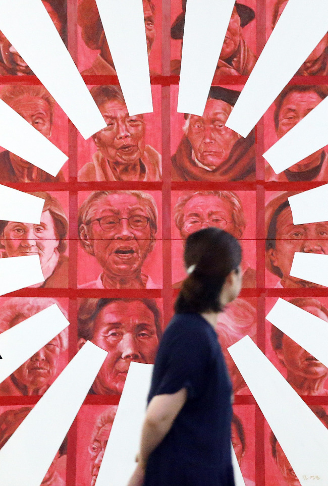A citizen looks at an artwork depicting the pain of former sex slaves under Japanese colonial rule during an exhibition at Seoul City Hall. (Yonhap)