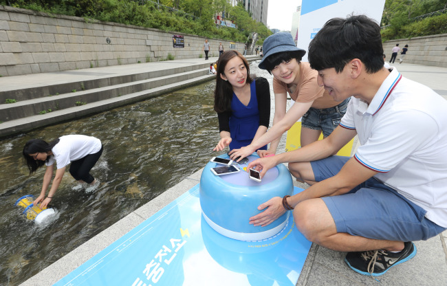 Employees from a venture start-up present a smartphone battery charging station at Cheonggyecheon Stream in Seoul on Wednesday. (Yonhap)