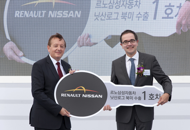 Renault Samsung Motors CEO Francois Provost (right) and Pierre Loing, vice president and product strategy and planning at Nissan America, celebrate the first shipment of the Nissan Rogue from the Korean carmaker's Busan plant on Friday. (Renault Samsung Motors)
