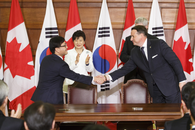 Korea Forest Service Minister Shin Won-sop (left) shakes hands with Canadian Minister of Natural Resources Greg Rickford on Sept. 22 in Ottawa, Canada. The two countries signed a memorandum of understanding on forest cooperation during President Park Geun-hye's visit to meet Canadian Prime Minister Stephen Harper. (KFS)