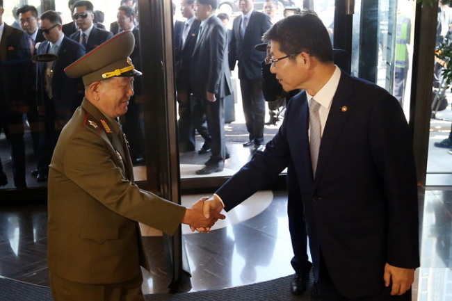 Hwang Pyong-so (left), director of North Korean military`s General Political Bureau, shake hands with South Korean Unification Minister Ryoo Kihl-jae at Incheon Oakwood Hotel on Saturday. (Yonhap)