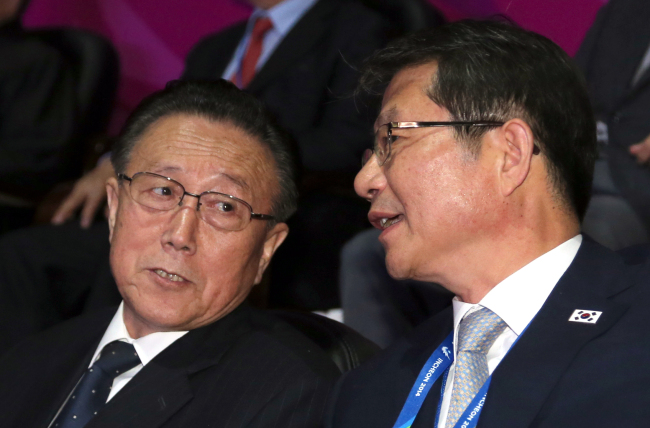 South Korea's Unification Minister Ryoo Kihl-jae (right) talks with Kim Yang-gon, director of the North Korean United Front Department of the ruling Workers' Party, during the closing ceremony of the Asian Games at the Incheon Asiad Main Stadium on Saturday. (Yonhap)