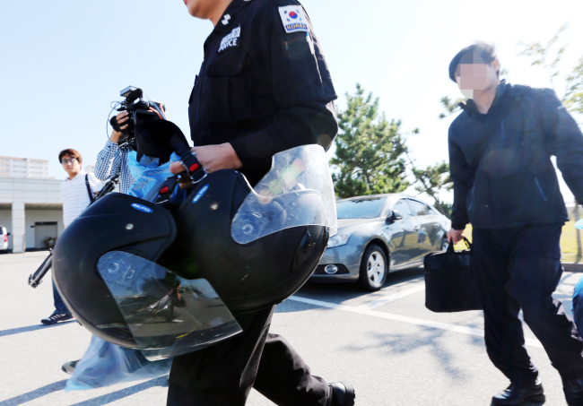 The Coast Guard officers head to the local police station for investigation on Friday, following the death of the captain of a Chinese fishing boat. (Yonhap)