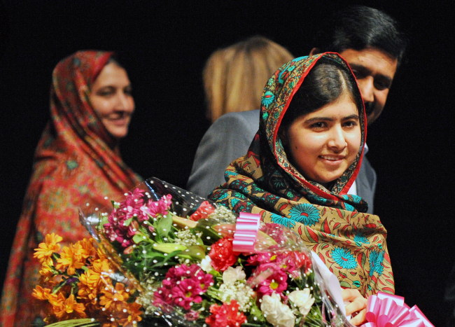 Malala Yousafzai holds flowers after speaking during a media conference at the Library of Birmingham, after she was named a cowinner of the Nobel Peace Prize, in Birmingham, England, Friday. (AP-Yonhap)