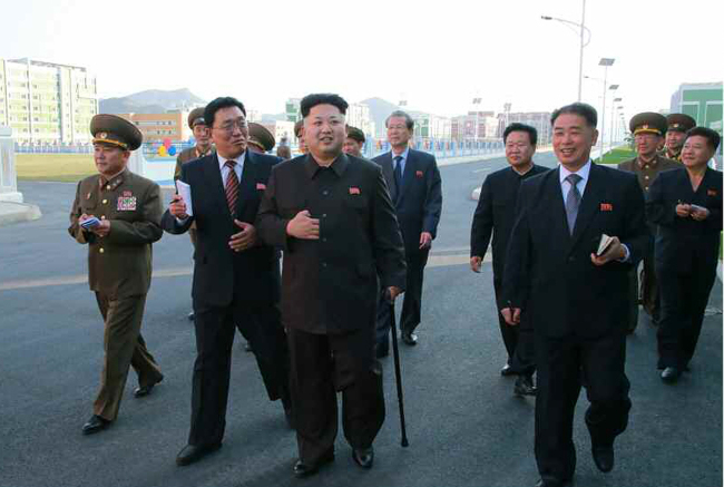 North Korean leader Kim Jong-un (third from left) is seen with a cane in a photo run Monday by the Rodong Sinmun about his trip to a residential district in Pyongyang. (Yonhap)