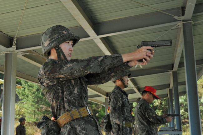 Chey Min-jung, daughter of SK Group chairman Chey Tae-won, fires a handgun during training at the Korea Naval Academy.