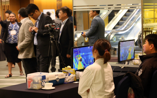 Officials at a forum organizing body monitor participants' body temperatures at a hotel in Seoul on Monday. (Yonhap)
