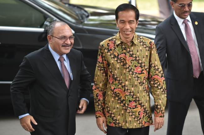 Indonesian President Joko Widodo (center) and Papua New Guinea Prime Minister Peter O'Neill walk together after their meeting in Jakarta on Tuesday. (AFP-Yonhap)
