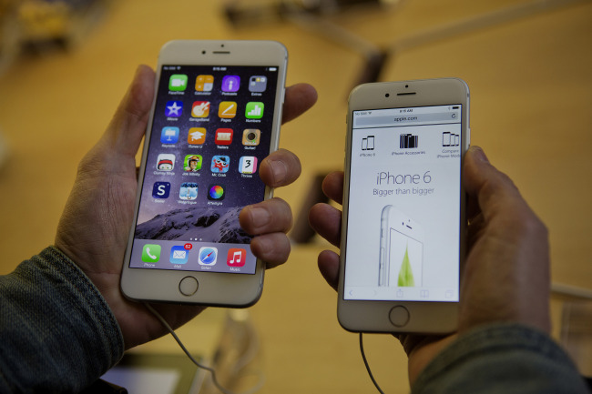 A customer tries to decide between an iPhone 6 Plus (left) and iPhone 6 during the sales launch at the Apple Inc. store in New York on Sept. 19. (Bloomberg)