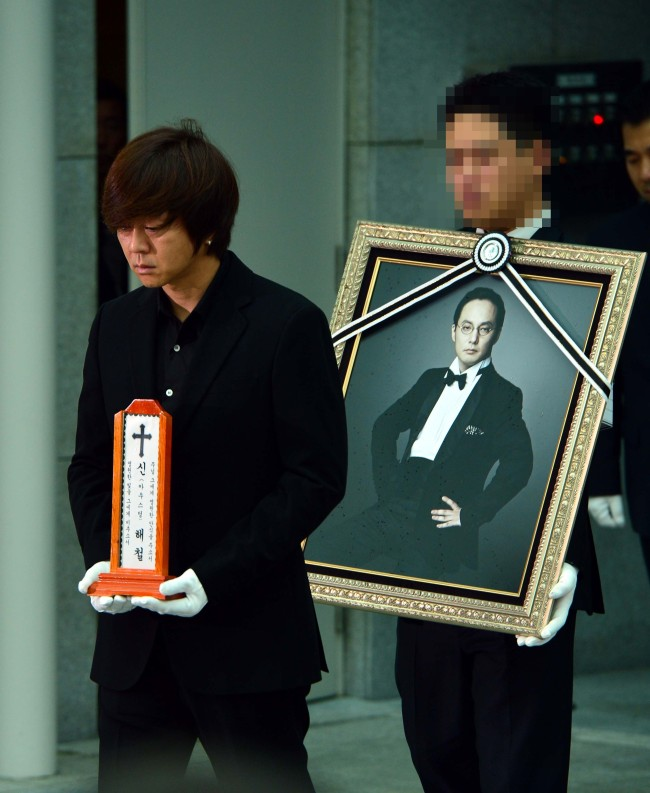 Singer Yoon Do-hyun holds the name plate of Shin Hae-chul as the singer's coffin is carried into a hearse during a funeral ceremony at Seoul's Asan Medical Center Funeral Home on Friday morning. (Yoon Byung-chan/The Korea Herald)