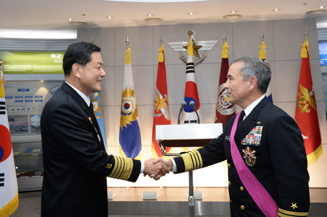 U.S. Pacific Fleet Commander Adm. Harry B. Harris (right) shakes hands with South Korea's Chief of Naval Operations Adm. Hwang Ki-chul, after receiving Seoul's national security medal at the Ministry of National Defense in Seoul on Monday. (Navy)