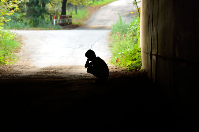 An underprivileged child squats at the entrance of a tunnel.(123RF)