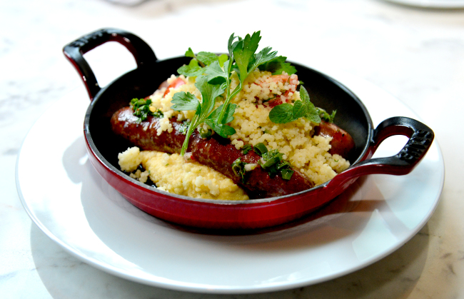 La Cave du Cochon's merguez sausage — crafted with lamb, harissa and cumin — is served laid over a bed of hummus, topped with couscous, parsley and mint (Yoon Byung-chan/The Korea Herald)