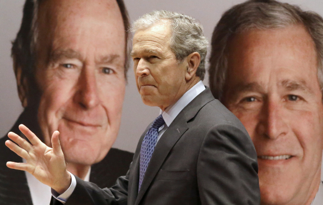 "Former President George W. Bush passes by a portrait of himself and his father former President George H.W. Bush as he takes the stage to discuss his new book, ""41: A Portrait of My Father"" at his father's presidential library in College Station, Texas, Tuesday. (AP-Yonhap)"
