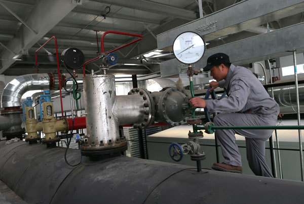 A worker examines equipment in a gas-fired plant in Beijing. Traditional coal-fired plants are switching to natural gas to generate power and supply heat for households from November in the capital. (Xuan Jun/China Daily)