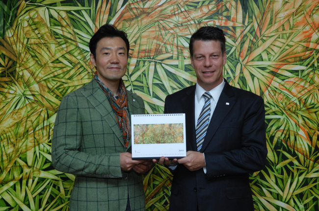 Michael Grund (right), managing director of Merck Korea, poses with Korean painter Kim Geon-il at an event to unveil the company's 2015 calendar featuring the artist's paintings in Seoul on Tuesday. (Merck Korea)