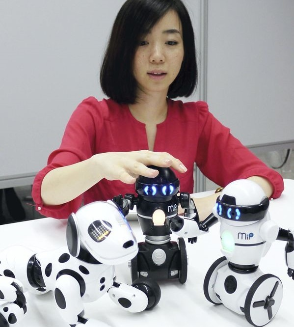 """Tomy Co.'s robot dog """"Hello! Zoomer"""" (left) and two humanoid robots, """"Hello! Mip"""" (center and right)."""