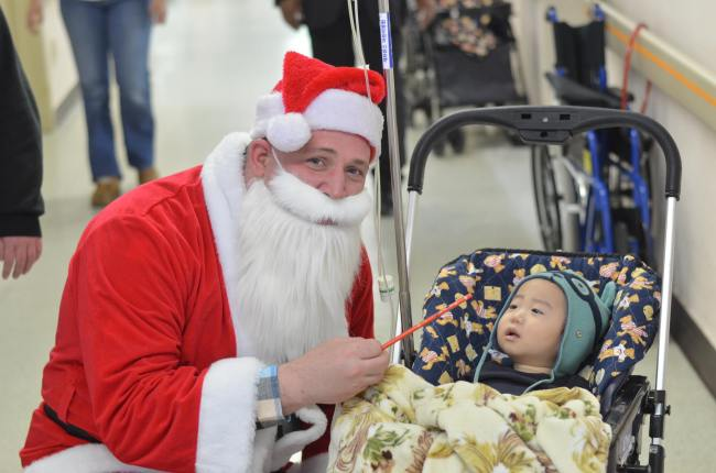 A volunteer dressed as Santa visits a baby in the cancer ward of Severance Hospital in Seoul during a volunteering event held last year by HOPE. (HOPE)