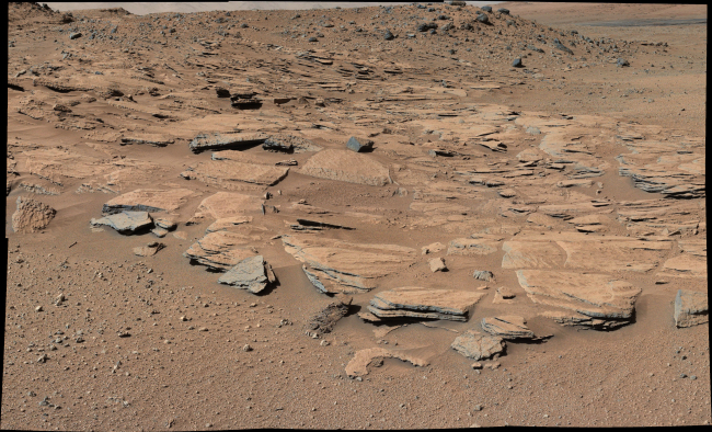 """This image taken by the Mast Camera on NASA's Curiosity Mars rover just north of the """"Kimberley"""" waypoint shows beds of sandstone inclined to the southwest toward Mount Sharp and away from the Gale Crater rim (top photo). The inclination of the beds indicates a build-out of sediment toward Mount Sharp. These inclined beds are interpreted as the deposits of small deltas fed by rivers flowing down from the crater rim to the north and building out into a lake to the south, where Mount Sharp is now. (NASA)"""