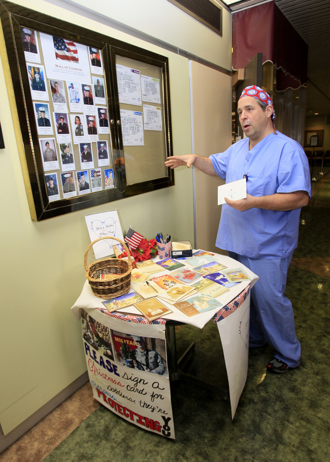 Tom Stiles, a surgical assistant at Summa Barberton Hospital, talks about his effort to send holiday cards to those in military service overseas as he stands next to a table he set up for people to write cards to members of the military at the entrance of the hospital in Barberton, Ohio on Nov. 19. (Akron Beacon Journal/TNS)