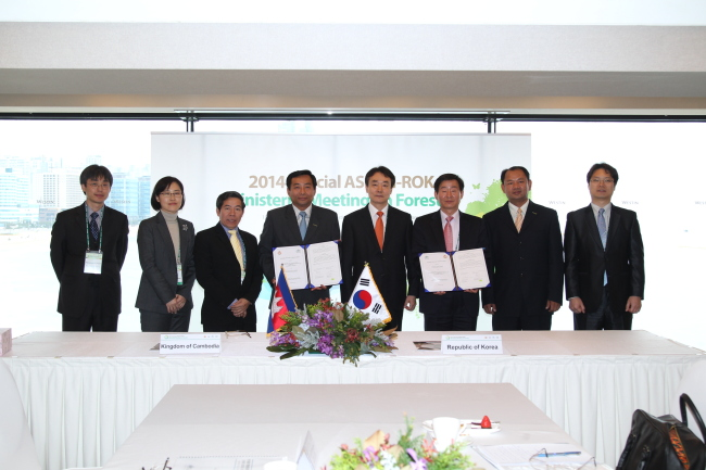 Cambodian Forest Minister Chheng Kimsun (fourth from left), Kim Yong-ha (fifth from left) and Lee Chang-jae of the KFS (third from right) pose after Korea and Cambodia signed an MOU on promoting a United Nations-led program on reducing emissions from deforestation and forest degradation in developing countries. (KFS)