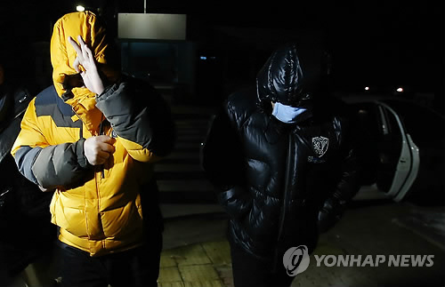 Two police officers suspected of leaking presidential document leave Seoul Detention House in Uiwang on Friday. (Yonhap)