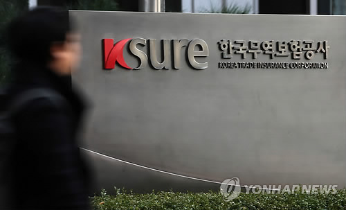 A pedestrian walks past the headquarters of K-sure in Seoul. (Yonhap)